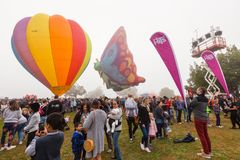 Hot air balloons, one shaped like a butterfly, hovering over a crowd royalty free stock photo