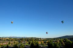 Hot Air Balloons Over Bend Oregon. Three bright hot air balloons flying in the blue sky over the city of Bend, Oregon for Balloons Over Bend event Royalty Free Stock Image