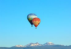 Hot Air Balloons Over Cascade Mountains. Two bright colorful hot air balloons flying over the Cascade Mountain Range in Oregon Stock Image