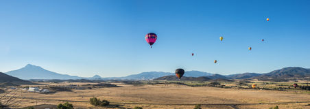 Hot air balloons over fields with Mt. Shasta. Hot air balloons rise over the fields near Montegue California on a clear morning with Mt. Shasta in the distance Stock Photos