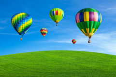 Hot air balloons over green field Stock Photos