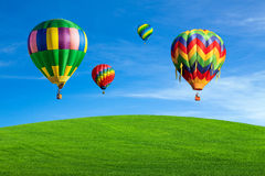 Hot air balloons over green field Stock Image
