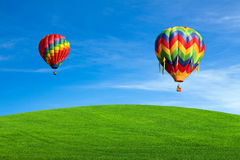 Hot air balloons over green field Royalty Free Stock Photography
