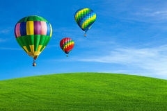 Hot air balloons over green field Stock Photography