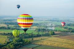 Hot air balloons over green rice field Stock Photos