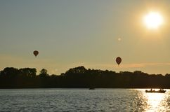 Hot air balloons over a lake in Poland view during sunset stock photography