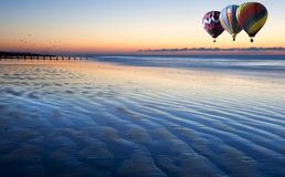 Hot air balloons over low tide beach at sunrise. Beautiful low point of view along beach at low tide out to sea with vibrant sunrise sky with hot air balloons Stock Photo