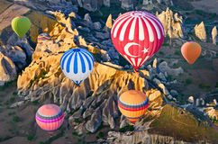 Hot air balloons over mountain landscape in Cappadocia, Turkey