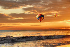 Hot air balloons over sunset beach. Two Hot air balloons flying over a  sunset beach Stock Photo