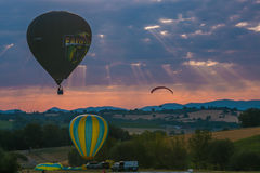 Hot air balloons and paragliding flying at sunrise in Umbria Stock Images