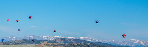 Hot Air Balloons passing over mountains in Colorado Stock Photo