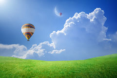 Hot air balloons rise up into blue sky to new moon Royalty Free Stock Photo