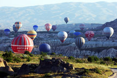 Hot air balloons rise in a wave from Rose Valley as the sun rises near Goreme in the Cappadocia region of Turkey. Stock Image