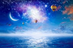 Hot air balloons in sky with bright stars, crescent. Tranquil heavenly picture - colorful hot air balloons flying in blue starry sky with bright stars, new moon Royalty Free Stock Photo