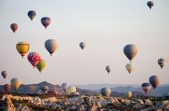 Hot air balloons at sunrise flying over Cappadocia, Turkey. A balloon with a flag of Turkey.  royalty free stock photos