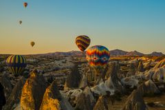 Hot air balloons at sunrise flying over Cappadocia, Turkey. A balloon with a flag of Turkey. stock photography