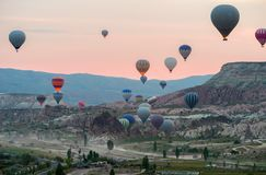 Hot air balloons take off before sunrise near the Goreme in the Cappadocia, Turkey stock photography