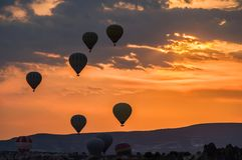 Hot air balloons take off at sunrise over Cappadocia, Goreme, Turkey stock photography
