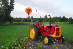 Hot Air Balloons and Tractor. Hot Air Balloons over a field and an old tractor Royalty Free Stock Photos