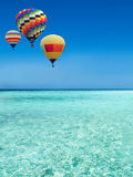 Hot air balloons travel over the sea. Colorful hot air balloons flying over the blue sea Royalty Free Stock Photography