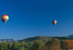 HOT AIR BALOON. S flying over  hills Stock Photos