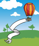 Hot air baloon. Hot air balloon with a huge banner, in a natural green landscape Royalty Free Stock Photography