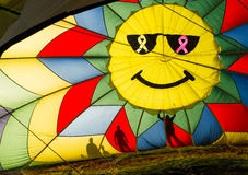 Hot air baloon with smile being inflated on the ground. Hot air baloon with silhouettes of people inflating it Stock Photography