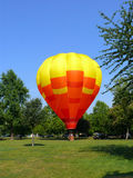 Hot air baloon takeoff. Red yellow hot air balloon taking off from a park. Green grass and trees surround it. Two people in the basket Stock Photos