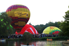 Hot air baloons flying in the evening sky near the lake Stock Image