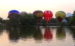 Hot air baloons flying in the evening sky near the lake Royalty Free Stock Images