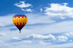 Hot air colorful ballon against blue sky with white fluffy cloud. S and copyspace for text stock photos