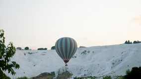 Hot air colorful balloon fly over the white limestone mountains. In the morning on a warm summer day stock video footage