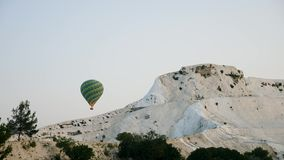 Hot air colorful balloon fly over the white limestone mountains. In the morning on a warm summer day stock video