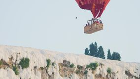 Hot air colorful balloon fly over the white limestone mountains. Turkey, Pamukkale - 12 June 2019: Hot air colorful balloon fly over the white limestone stock video footage