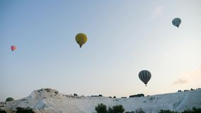 Hot air colorful balloon fly over the white limestone mountains. Turkey, Pamukkale - 12 June 2019: Hot air colorful balloon fly over the white limestone stock footage