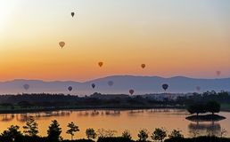 Hot air colorful Balloon flying in the sunrise morning Stock Photos