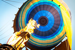 Hot air from a gas burner fills the dome of the balloon Stock Images