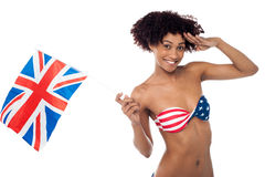 Hot American bikini model saluting and waving UK flag Stock Image