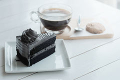 Hot americano black coffee and A piece of charcoal cake on white wooden table. Have some space foe write wording stock images