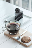 Hot americano black coffee and A piece of charcoal cake on white wooden table. Have some space foe write wording Stock Image
