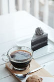 Hot americano black coffee and A piece of charcoal cake on white wooden table. Have some space foe write wording Royalty Free Stock Photo