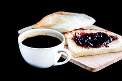 Hot americano, Black coffee in white cup and bread with jam on wooden background Stock Images
