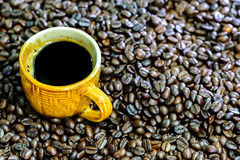 Hot americano, Black coffee in yellow cup with coffee beans. Royalty Free Stock Photography