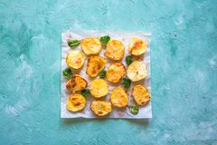 Hot appetizing baked potatoes halves on parchment. stock images