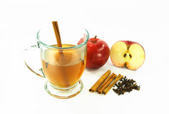 Hot apple cider in glass over white. Glass of hot apple cider spiced with cinnamon stick and cloves - spices cinnamon sticks, cloves and raw apples for Royalty Free Stock Images