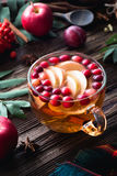 Hot apple cranberry cinnamon tea in cup on wooden table. Warming winter berry tea with cranberries, apple, cinnamon, lemon, honey and thyme in a glass cup on Royalty Free Stock Image