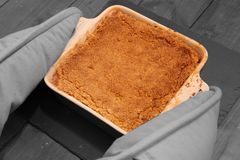 Hot apple crumble being put on slate mat Stock Photography