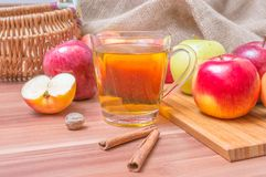 Hot apple drink cider and apples with cinnamon on table Stock Image