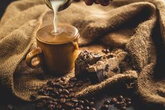 Hot Arabica coffee in brown glass and coffee beans on sack. And blackbord Royalty Free Stock Photography