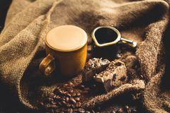 Hot Arabica coffee in brown glass and coffee beans on sack. And blackbord Royalty Free Stock Image